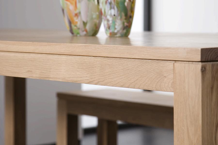 Et hjørnebord er både hyggeligt og giver rummets hjørner muligheden for at blive en hyggekrog i hjemmet, som her med et spisebord fra Ethnicraft.
