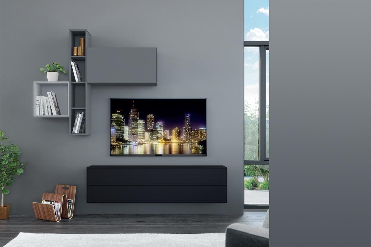 Et vægophængt tv-møbel med et fladskærms tv.
