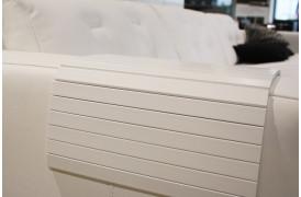 Dette er et billede af en armlænsbakke i hvid placeret på en sofa.