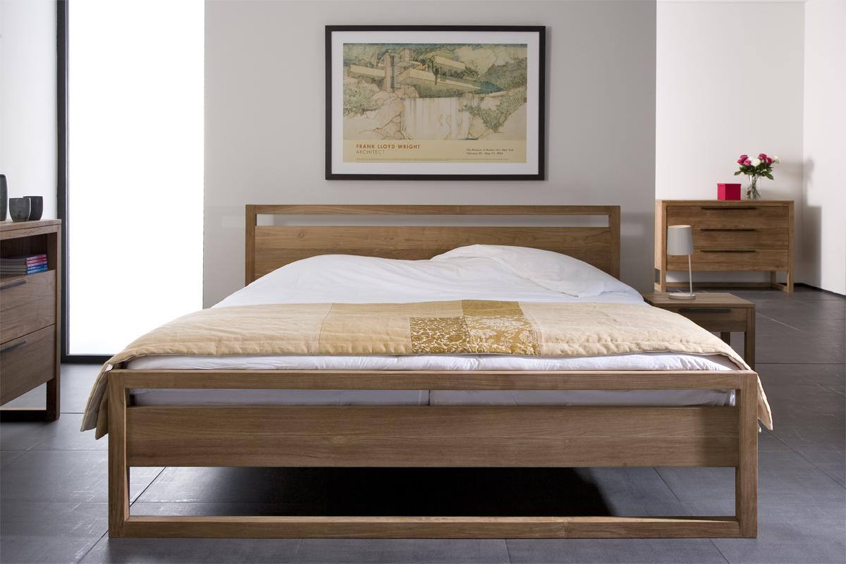 En sengeramme i træ står flot i et soveværelse på dette billede.