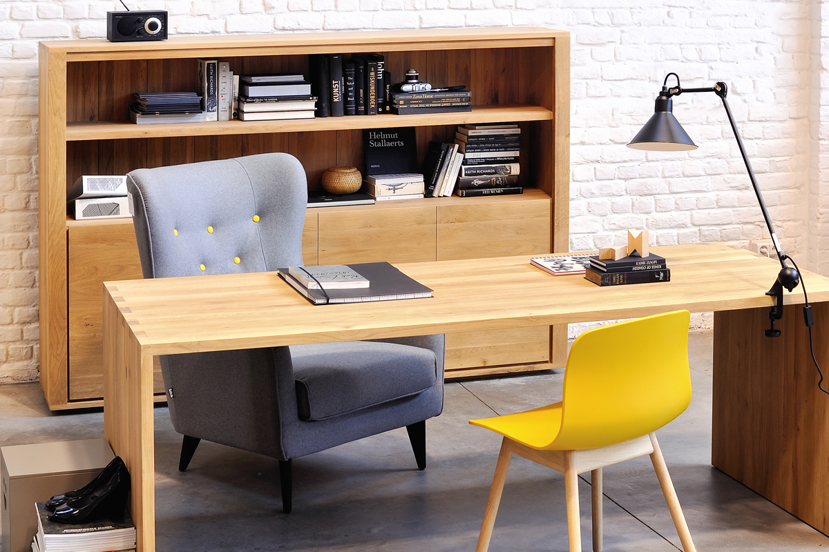 Et skrivebord i træ er her på billedet placeret i et kontormiljø.