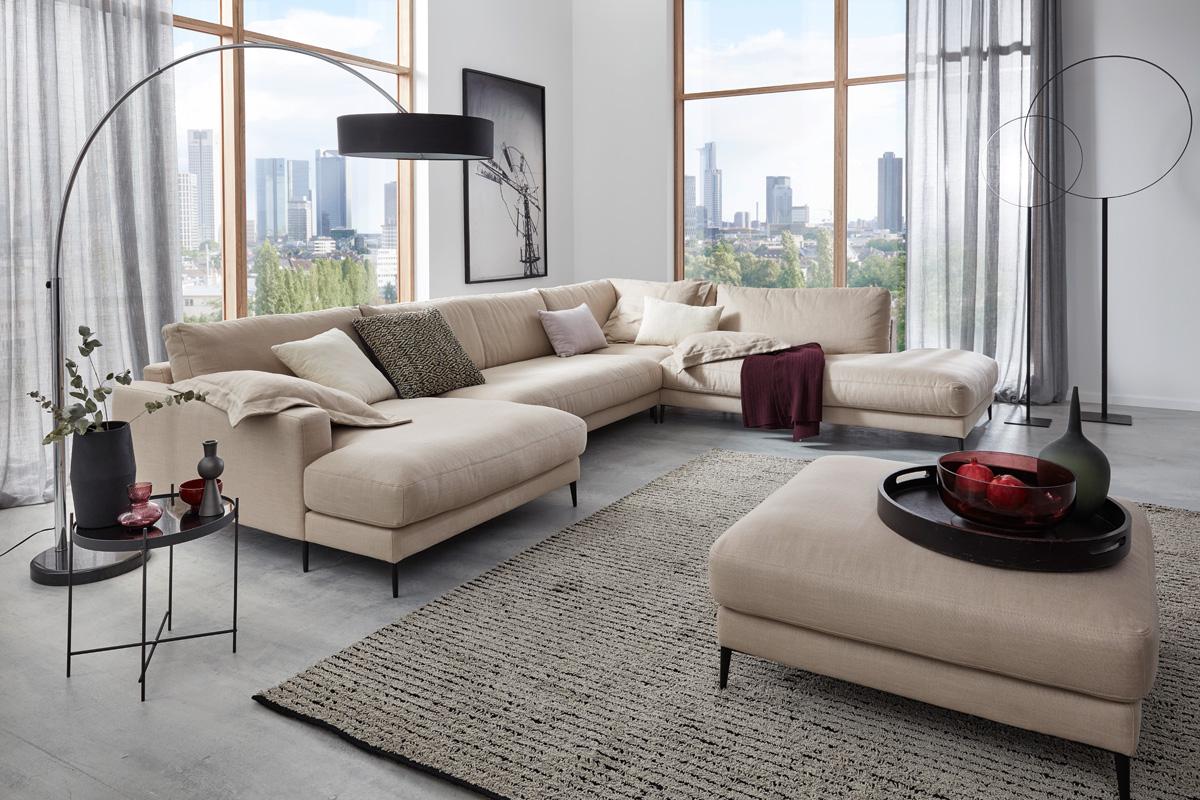 Det med at finde placeringen af en sofa i en stue er ikke altid helt let. Som en generel regel skal sofaen vende mod kontaktpunktet i rummet, hvor den er placeret, men hvis der ikke er noget naturligt omdrejningspunkt, hvad gør du så? Her er nogle tips til sofaplacering, der hjælper dig med at finde ud af det. Her ses Uptown sofaen fra Indomo placeret langs nogle vinduer i en stue.