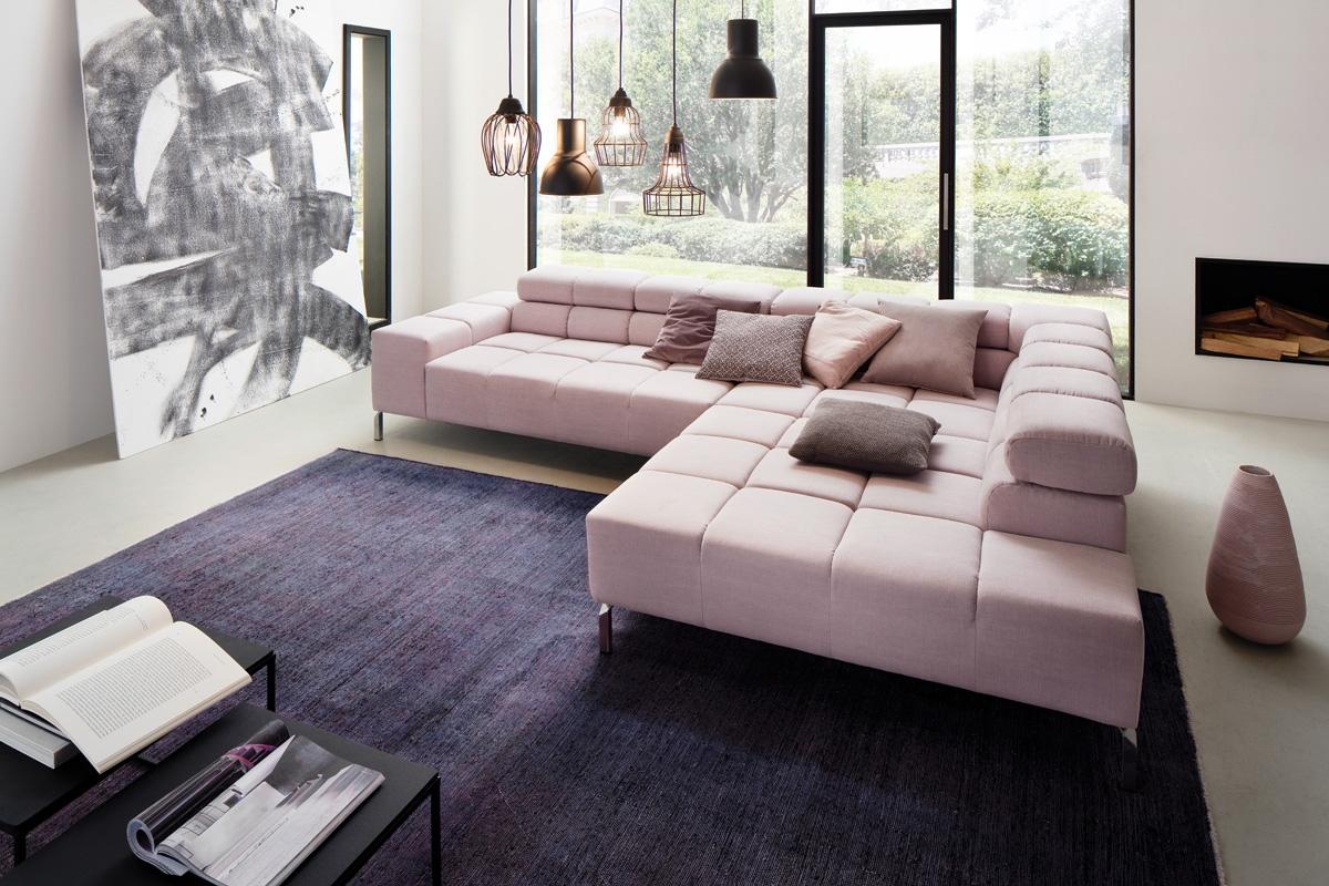 En stilfuld sofa står her placeret i en bolig. Sofamodellen Wilson indeholder klassisk stil og top design og dens rene linjer er stilfulde, hvilket giver et overordnet struktureret udseende, hvor de fine syninger sæder og armlæn er lavet i mikrosektioner, hvilket giver et helt nyt og spændende udseende. Du kan købe sofaen her hos BoShop.