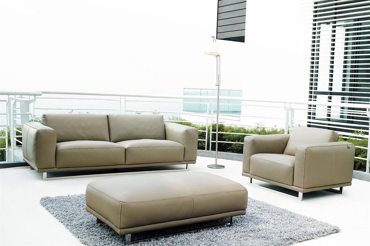 Billedet viser en sofa med puf, hvor puffen er placeret foran sofaen ude i rummet.