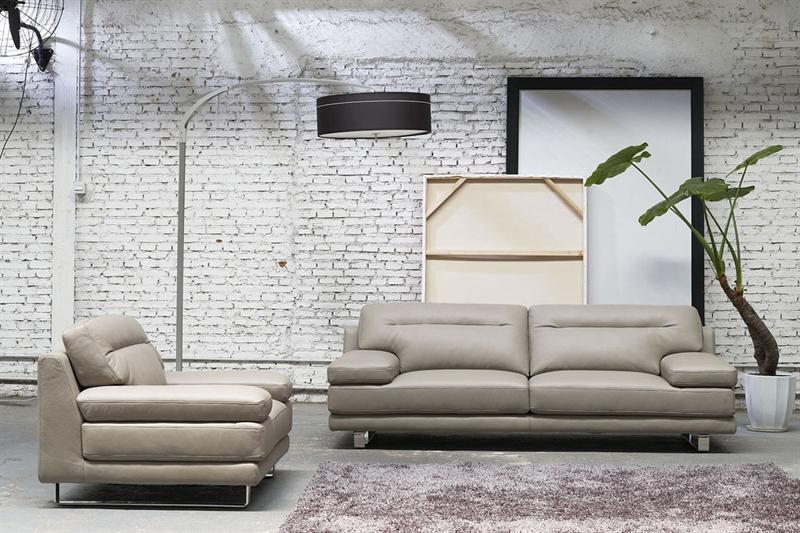 Et par lædermøbler i en grå farve ses her i en boligindretning.