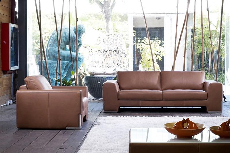 Brun lædersofa med tilhørende lænestol ses her på billedet i en bolig.