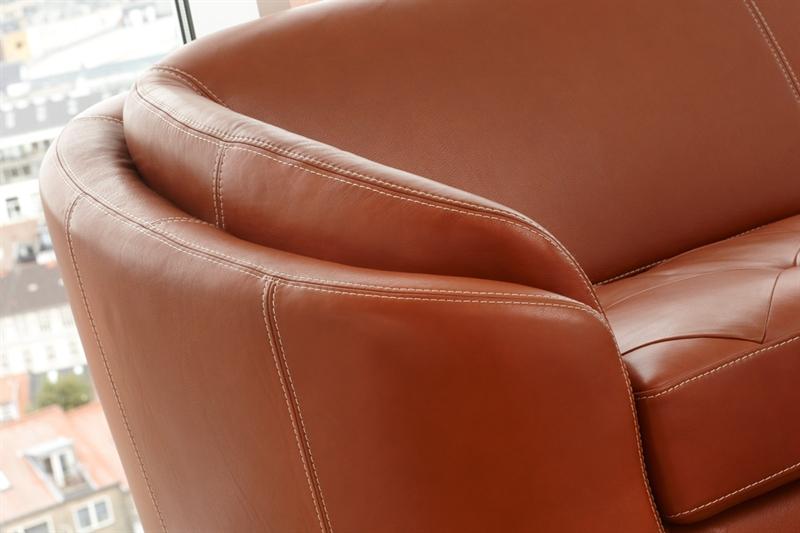Cognacfarvet sofa i læder står her placeret flot i en stue på dette detaljebillede. Billedet viser Rusco ll lædersofaen fra Kelvin Giormani, som du kan købe her hos BoShop, og fås som det ses på billedet i cognacfarvet læder med et flot og varmt farvespil i læderets glød.