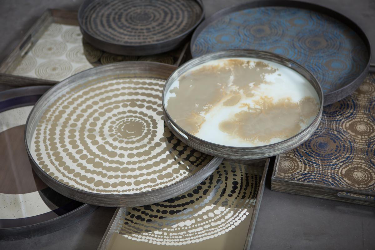 Både de runde og de rektangulære bakker fra Ethnicraft har serveringshanke, så man kan bære dem rundt.