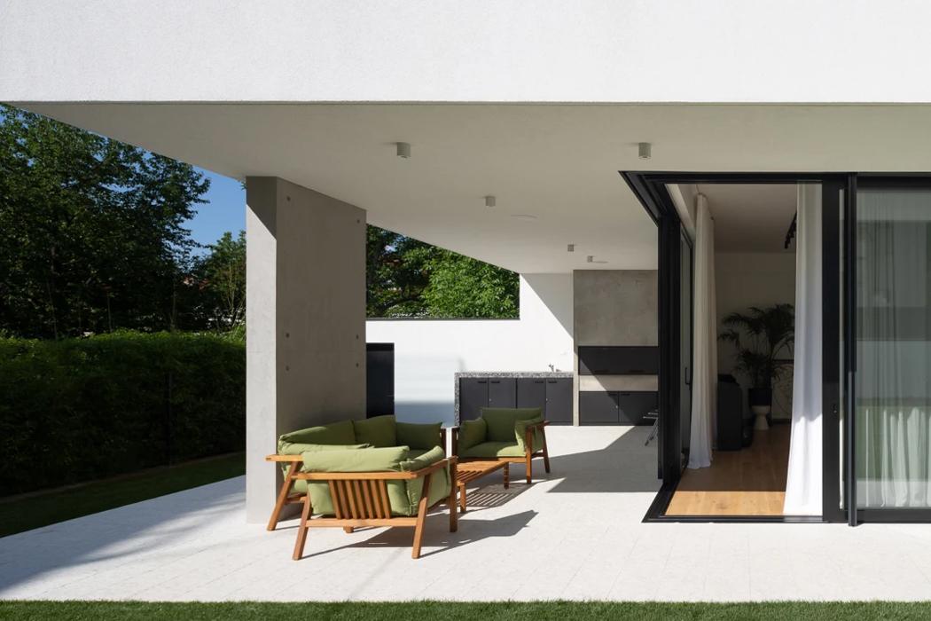 En overdækket terrasse med Prostorias Umomoku kollektionen, der her består af en havesofa, lænestol og et havebord. Hos BoShop finder du et bredt udvalg af luksus havemøbler og andre funktionelle ting til terrassen i super kvalitet og flot design.