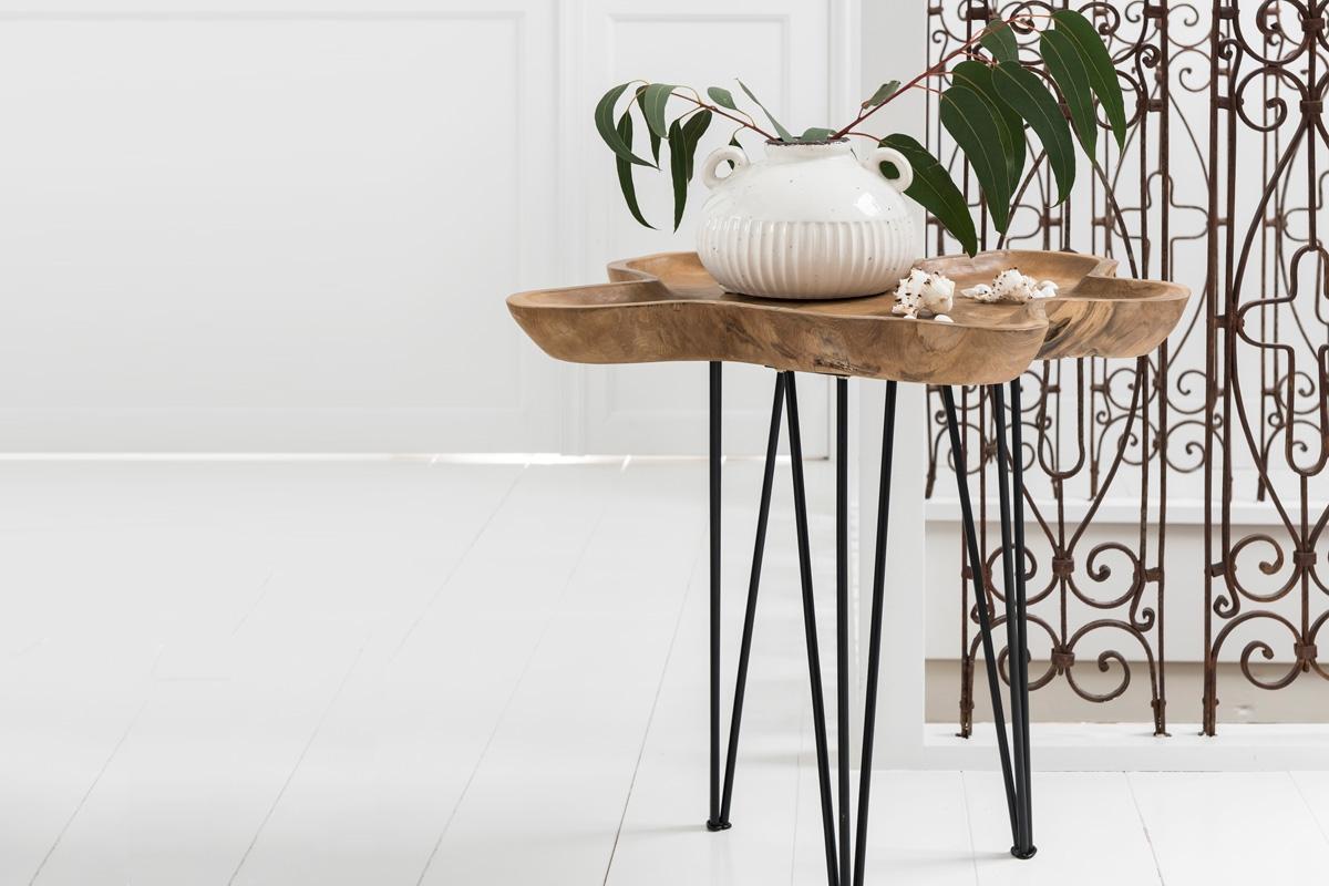 Et rustikt sidebord kombinerer traditionelt håndværk med moderne former. Bordbenene er bøjet af smedejern og bøjede i en træbordplade i mørkebrun, hvor træpladen er blevet fastspændt sammen i en simpel form og understøttes af simpel konstruktion.