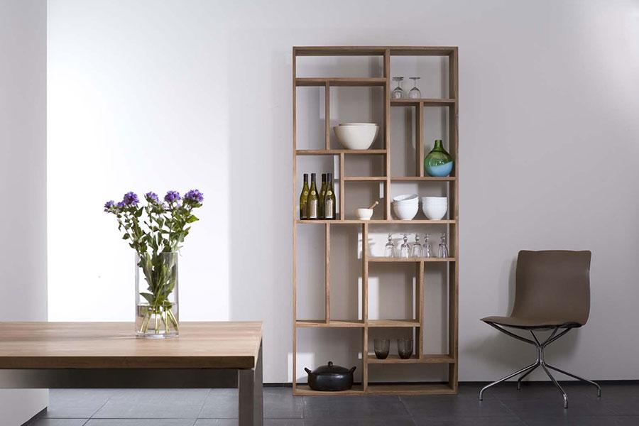 Med en reol og rumdeler i træ kan du opbevare dine ting med stil i boligen.