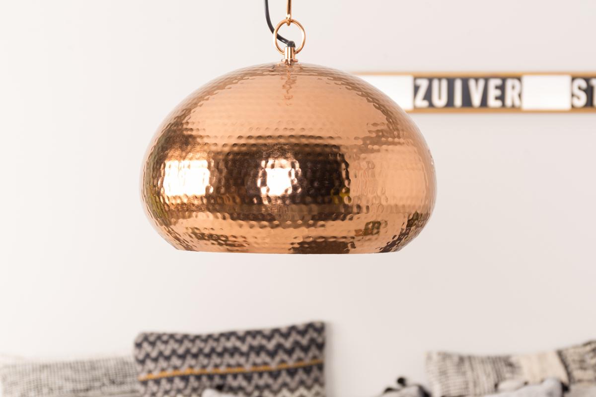 Kobberfarven på lampen har et varmt udtryk i sit visuelle materiale.