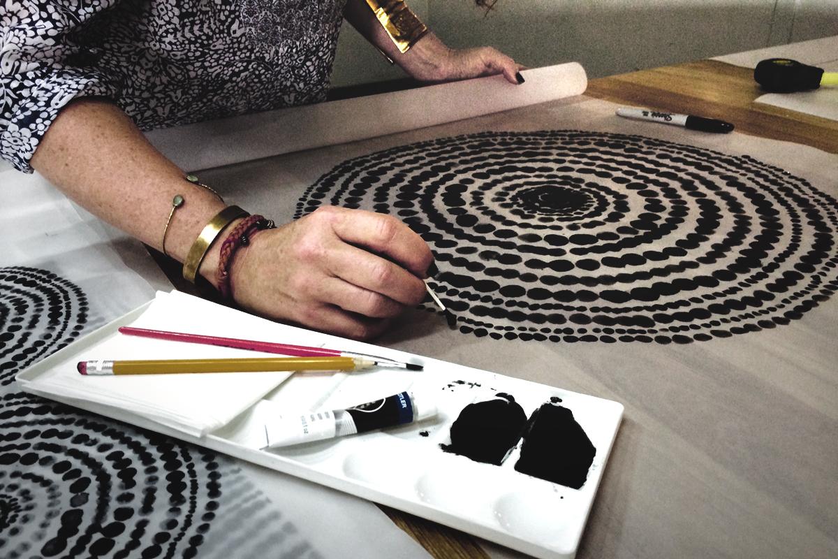 Her er kunstneren og designeren Dawn i gang med at lave mønstret 'Gold Beads', som du kan købe på nogle af de runde bakker fra Notre Monde.