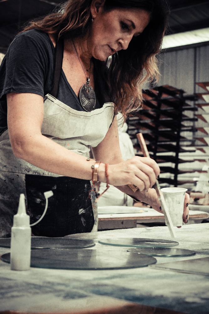Dawn Sweitzer står her i sit værksted og er ved at male på nogle af produkterne fra Notre Monde. Hun laver kun de ting, som hun selv synes bedst om og de ting, der betyder mest for hende. På den måde kommer der mest autencitet og ægthed ind i produkterne.