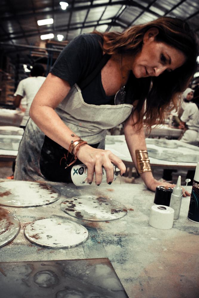 Dawn er egentlig med en oprindelse fra Amerika, men hun har teamet op som det belgiske firma Notre Monde om at lancere og udbrede det kommercielle kendskab til hendes kunstneriske kreationer. Her er hun på et værksted, hvor hun er ved at spraymale nogle ting.